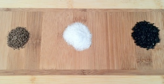 Image of smoked salt, kosher salt, and lava salt on a wooden cheese board.