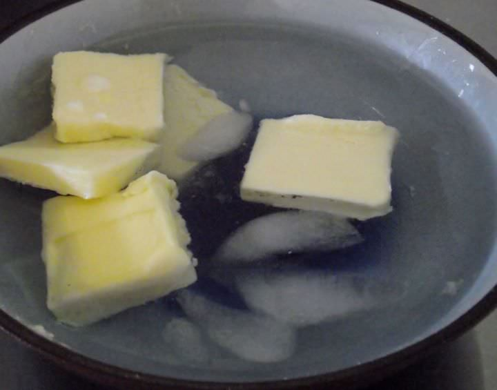 Butter squares floating in ice water.