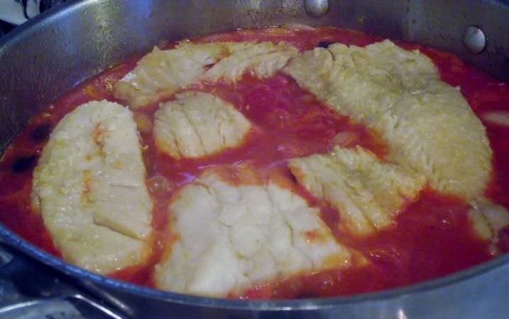 Salt cod braising in a tomato sauce.