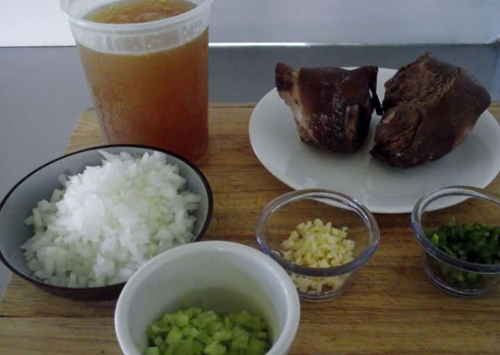 Ingredients for baked beans: chicken stock, smoked ham hocks, onions, garlic, celery, and jalapeno chilies.