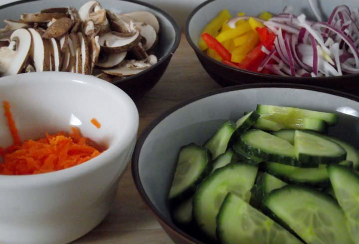 Sliced vegetables for the salad: mushrooms, carrots, red onions, and red and yellow peppers.