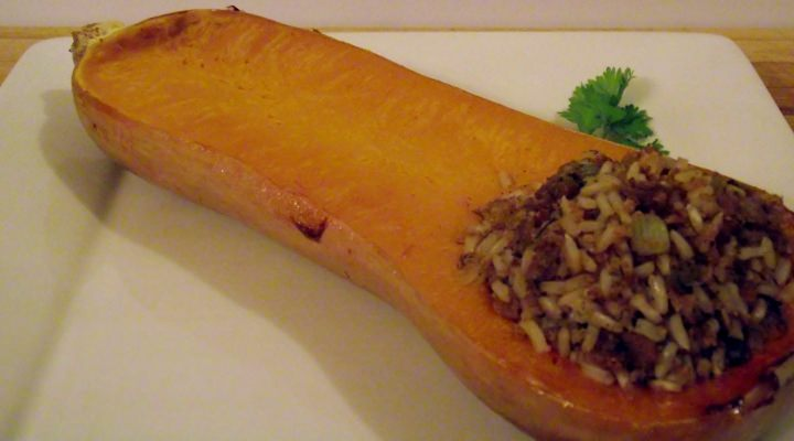 Sausage and rice stuffed butternut squash on a plate.