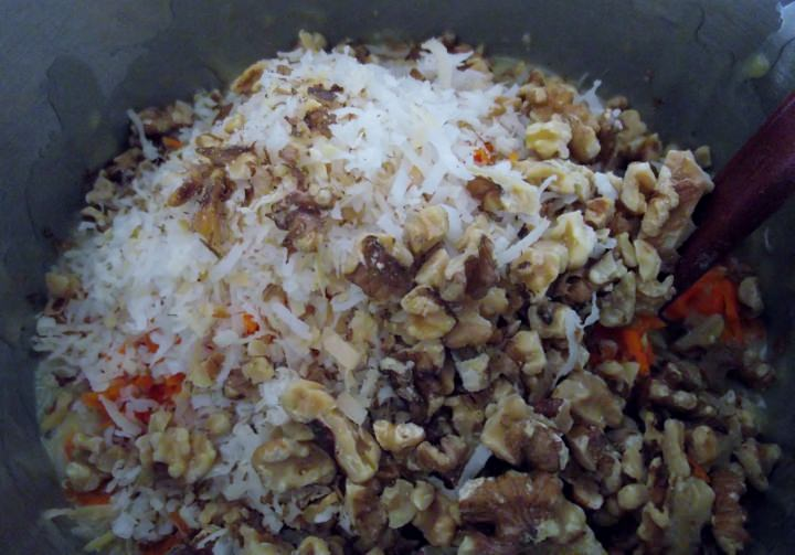 Adding the carrots, walnuts, and coconut to the cake batter.