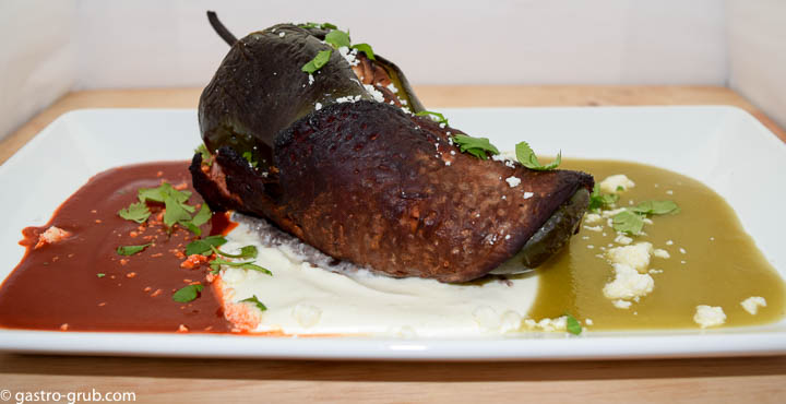 Chile relleno wrapped with flank steak and served with chili sauce, crema, and tomatillo sauce, on a rectangular plate.