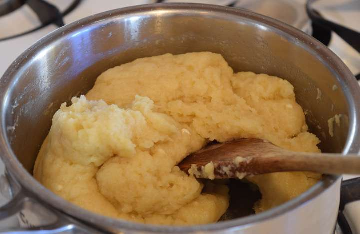 When the water milk mixture comes to a boil dump all the flour in at once. Immediately stir rapidly until the dough pulls away from the sides of the pot and forms into a ball.