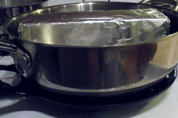 Here, I set a large saute pan on top of the breasts and weighted it down with a brick wrapped in foil.