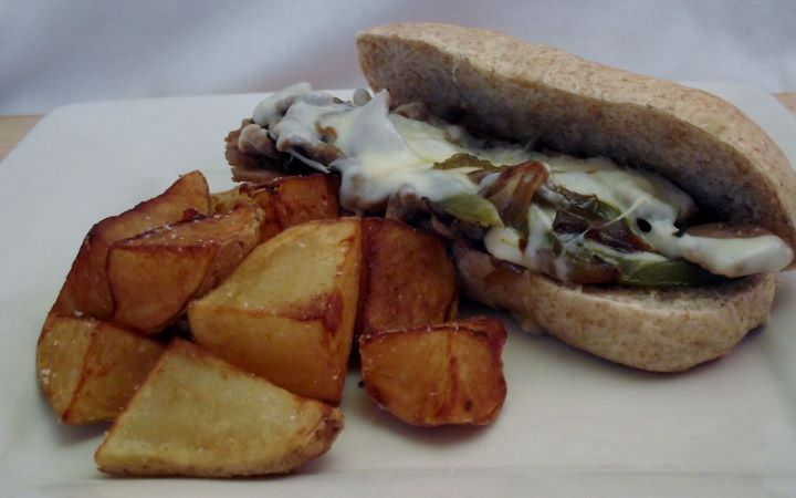 Philly cheese steak and fried potato wedges.