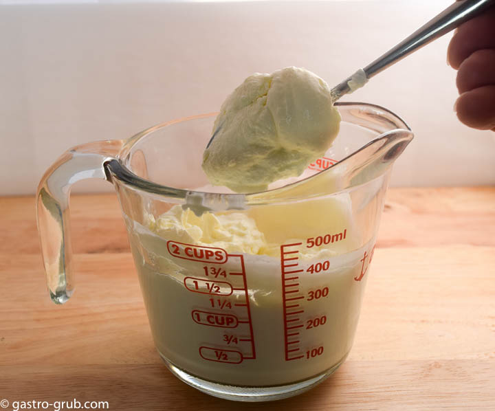 Mexican crema in a measuring cup.