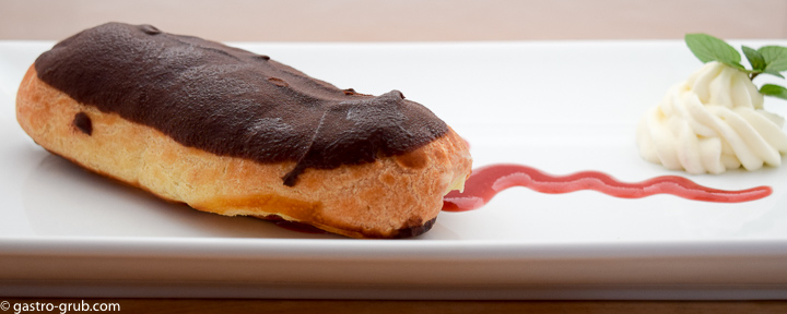 Chocolate eclair on a plate with with strawberry coulis and chantilly cream.