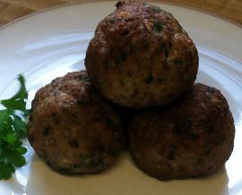 Meatballs on a plate with parsley.