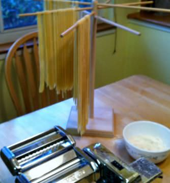 Homemade fettuccine hanging on a pasta rack.