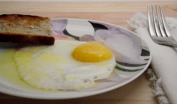 A fried egg with toast and butter.