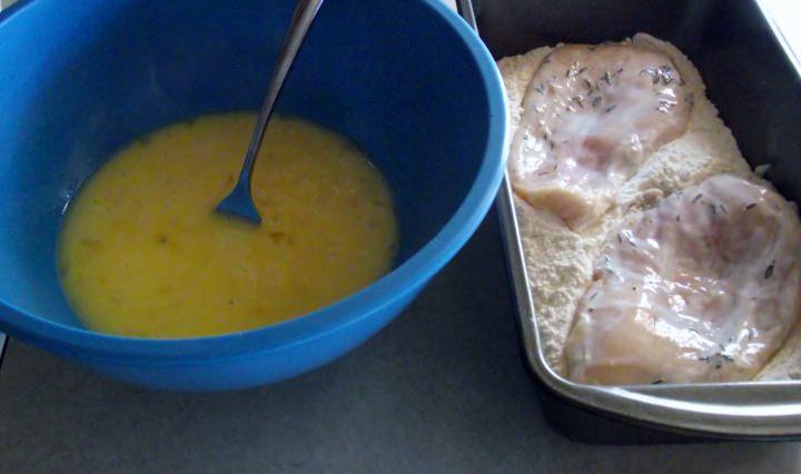 Dredging chicken breasts in flour.