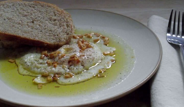 Garlic fried egg with olive oil and bread.