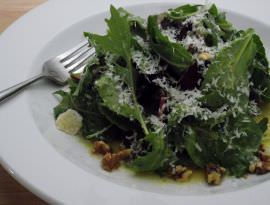 A green salad with shaved parmigiano.