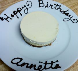 Cheesecake with happy birthday, Annette written in chocolate, on the plate.