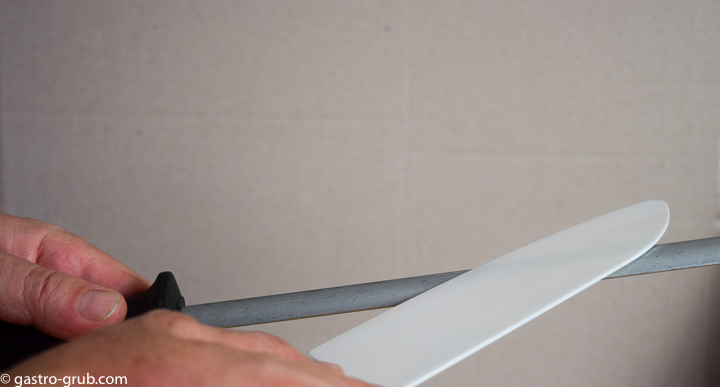Sharpening a ceramic knife with a diamond steel.