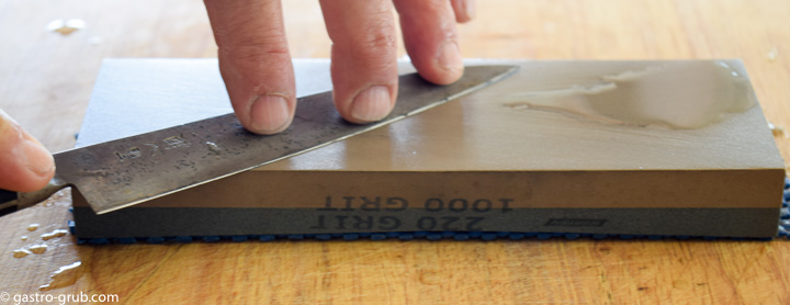 Sharpening a knife on a whetstone.