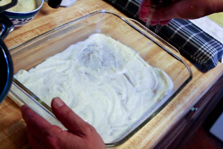 A 9 x 13 baking dish spread with bechamel.