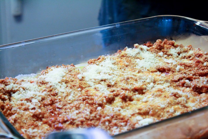 Building the lasagna by layering with sauce, pasta and cheese.