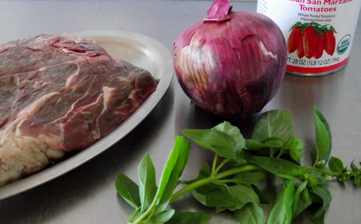 Ingredients for spaghetti sauce with meat: boneless chuck, red onion, fresh sweet basil, and San Marzano tomatoes.