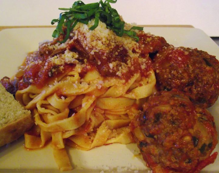 Homemade fettucine, spaghetti sauce with meat, Italian meatballs and rosemary bread.