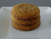 Stacked molasses cookies on a plate.