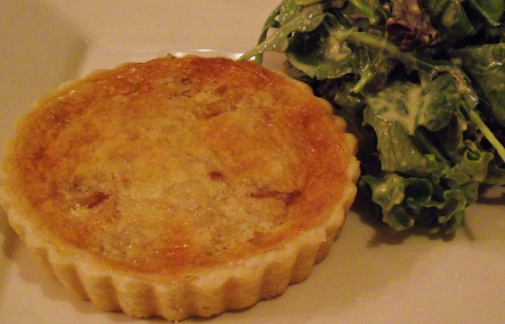 Onion and bacon tart on a plate with a green salad.