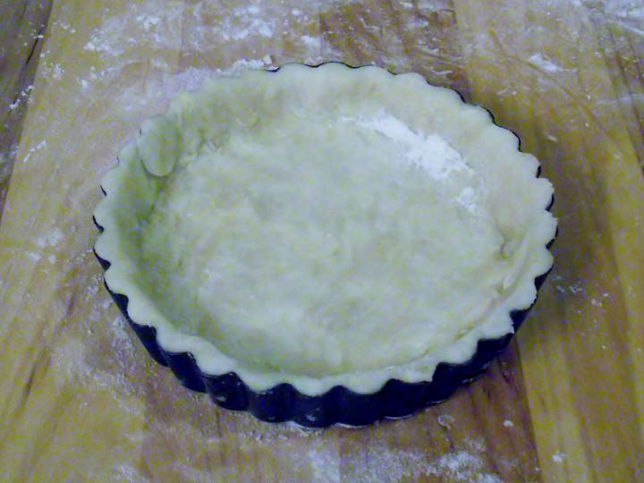 Pastry crust lining an individual tart pan.
