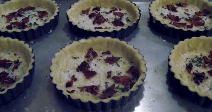 Individual tart pans with pastry, cheese, bacon, and thyme.