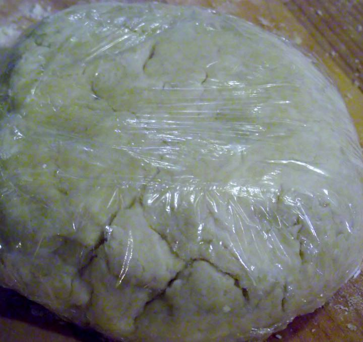 Pastry crust wrapped in plastic wrap.