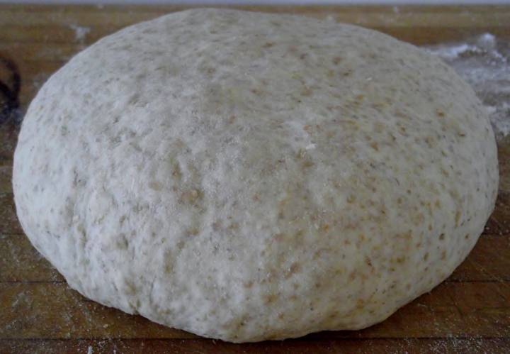 Pizza dough boule resting on a cutting board.