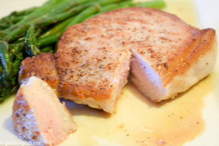 Pork chop and asparagus on a plate.