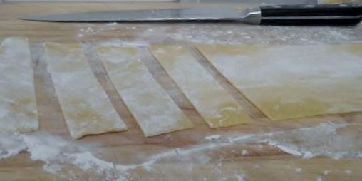 Cutting the rolled pasta into papperdelle.