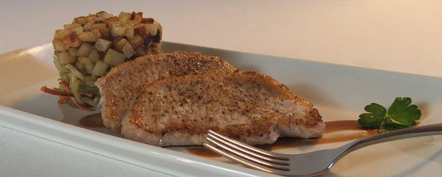Seared pork chops with stacked broccoli slaw and fried potatoes.