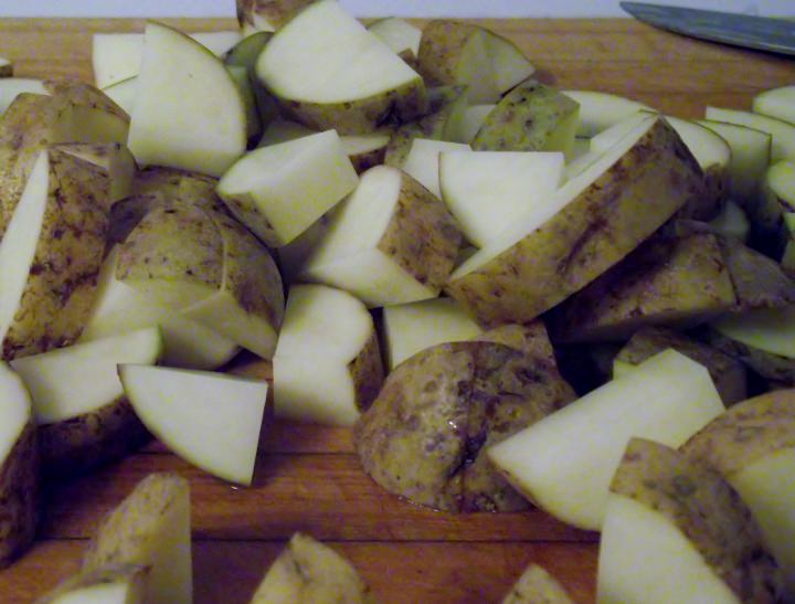 Potatoes on a cutting board quartered and sliced.