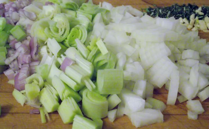 The aromatic vegetables and herbs: diced leeks, onion, shallot, garlic, celery, rosemary, and thyme.
