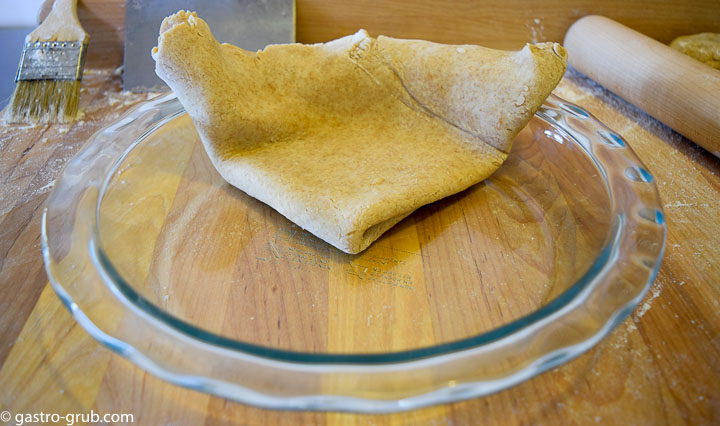 Pie dough being transferred to a pie plate, by folding it into fourths.