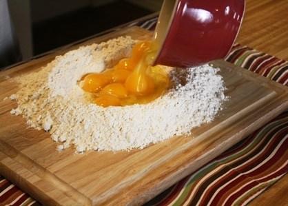 Adding eggs to flour for pasta.