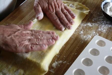 Layering sheets of pasta on a ravioli mould.