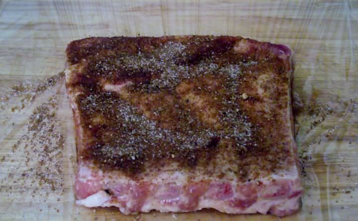 Pork rib section coated with dry rub.