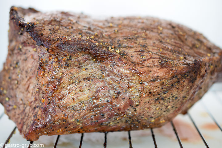 Roast beef cooling on a rack.