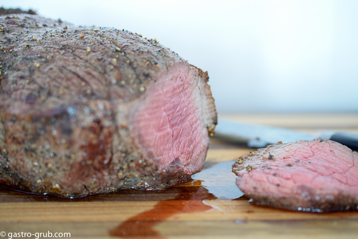 Roast beef with the end sliced off, showing the pink color of the rare meat.