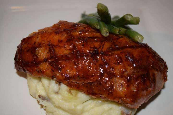 Glazed duck breast with mashed potatoes and green beans.