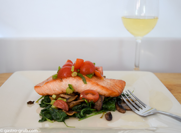 Seared salmon, sautéed mushrooms, and wilted kale with a cherry tomato relish.