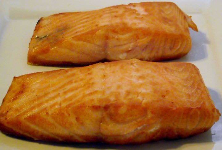 Seared salmon resting on a plate.