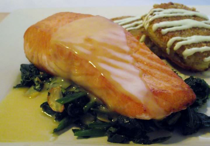 Seared Salmon with beurre blanc on top of sauteed greens and potato croquettes with green onion aioli.
