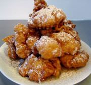 Sfinge or zeppole di San Giuseppe stacked on a plate with honey, cinnamon, and powdered sugar.