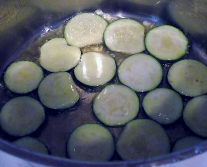 Zucchini frying in a pot.
