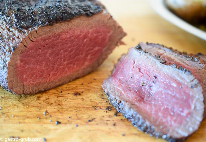 Tri tip roast slices showing the temperature and grain.